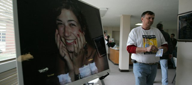 Curt Brungardt, father of slain Kansas University student Jana Mackey, passes by a portrait of his daughter in the United Way building on Sunday during the first observance of Jana Mackey Day. Volunteers completed a number of tasks related to Eleven Hundred Torches, a domestic violence prevention project established by Mackey's parents in her memory.