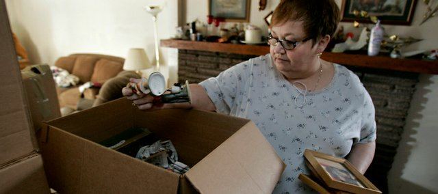 Rhonda Wagner packs some items last week at her home in Sacramento, Calif. Wagner, who works for the California Department of Motor Vehicles, and her family are losing their home to foreclosure. Wagner, 52, just absorbed a 9 percent pay cut because of a state-imposed unpaid leave.