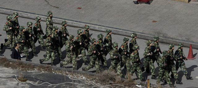 Tibetan monks walk by heavily armed paramilitary police today in Kangding, China. Authorities were on heightened alert today in Tibet and other areas of western China, tightening the security cordon for today's 50th anniversary of the failed uprising that sent the Dalai Lama into exile.