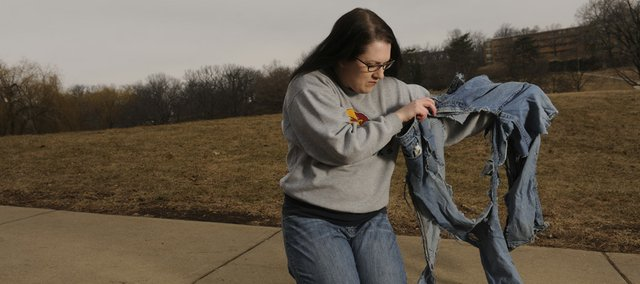 Traci Pillard holds the pair of jeans she was wearing when she was struck by lighting seven years ago at this spot.