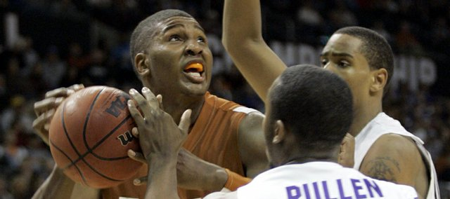 Texas' Dexter Pittman, left, is double-eamed by Kansas State's Jacob Pullen (0) and Ron Anderson, right, in the second half of their game at the Big 12 Conference men's tournament in Oklahoma City, Thursday, March 12, 2009.