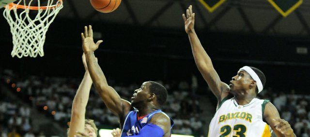 Kansas guard Sherron Collins lays up a shot between Baylor defenders Josh Lomers, left, and Kevin Rogers during the Jayhawks' victory on Feb. 2 in Waco, Texas. KU faces Baylor today in the Big 12 tournament.