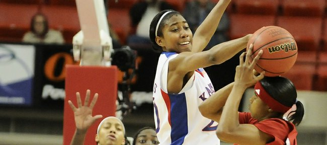 Kansas guard Sade Morris takes a swipe at the ball held by Nebraska guard Yvonne Turner during the first half Thursday, March 12, 2009 at the Cox Convention Center in Oklahoma City.