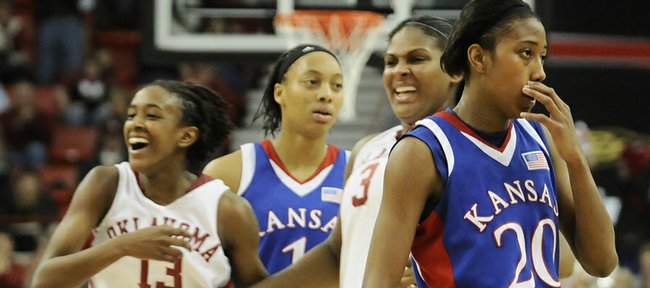 Kansas players Sade Morris, right, and Aishah Sutherland take a slow walk back to the bench as Oklahoma players Danielle Robinson, left, and Courtney Paris charge the court to celebrate with teammates during a timeout in the second half Friday, March 13, 2009 at the Cox Convention Center in Oklahoma City.