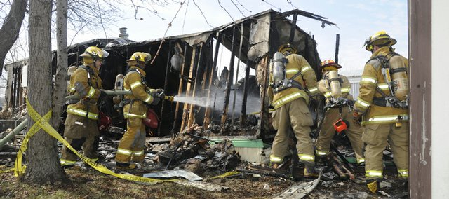 Firefighters extinguish flames that broke out around at a 1908 E. 19th St. home in the Brookwood Mobile Home Park in March.