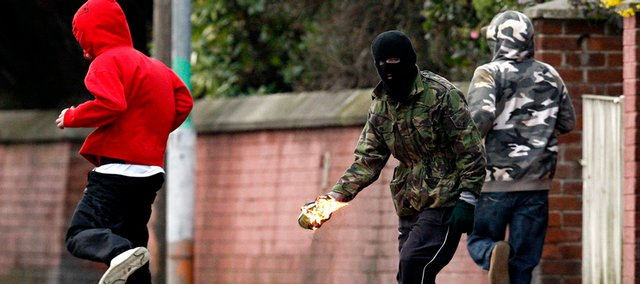 A masked youth prepares to throw a petrol bomb at police officers close to where a leading Irish Republican was arrested in connection with the recent murders of two British soldiers Saturday in Lurgan, Northern Ireland. Police arrested three suspected IRA dissidents, including a well-known Irish republican Saturday, on suspicion of killing two off-duty British soldiers, an attack designed to trigger wider violence in Northern Ireland.