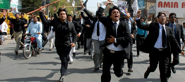 "Pakistani lawyers hold bamboo sticks as they run toward police officers during an anti-government rally Saturday in Multan, Pakistan. Pakistan's president urged opposition parties to negotiate an end to the country's political crisis while vowing to maintain law and order ""at all cost"" in the face of gathering anti-government protests."
