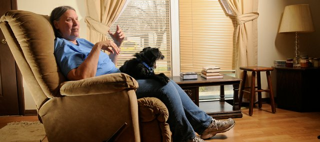 Debra Shirar has been waiting for almost 900 days to find out whether she will get disability insurance. In the meantime she is living with a friend, and with the help of some minimal state funding is holding on as best she can. Shirar sits with her friend's dog at their east Lawrence house.