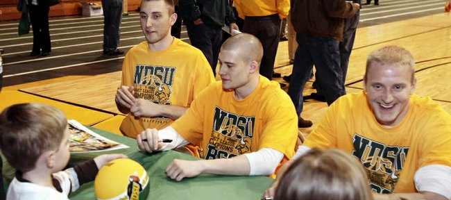 North Dakota State basketball players, from left, Lucas Moormann, Ben Woodside and Mike Nelson sign autographs for fans Sunday in Fargo, N.D., before the NCAA Tournament pairings were announced.