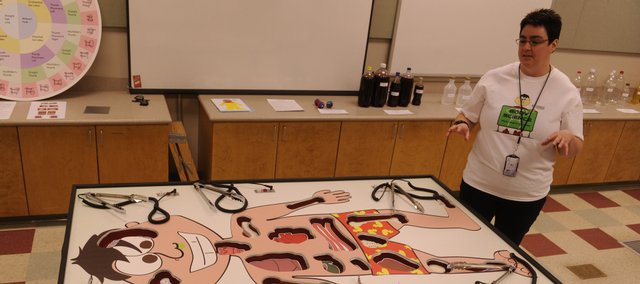 "Teresa MacDonald, director of education at the Kansas University Natural History Museum, shows off Anatomy Alex, a lifesize version of the ""Operation"" board game."
