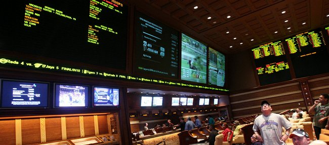 bettors watch the screens in the race and sports book at Wynn Las Vegas as the NCAA Tournament field is announced Sunday in Las Vegas.
