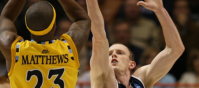 Utah State guard/forward Tyler Newbold (24) gets a hand in front of the shot of Marquette guard Wesley Matthews (23) during the second half of the first-round men's NCAA college basketball tournament game in Boise, Idaho, Friday, March 20, 2009. Marquette went on to win 58-57.
