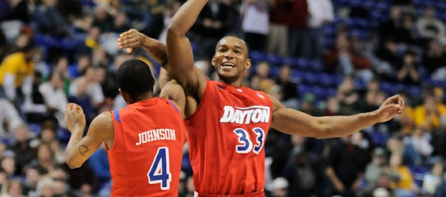 Dayton forward Chris Wright, right, gives teammate Chris Johnson a mid-air bump after a timeout is called by West Virginia during a Dayton run in the second half. The Flyers won, 68-60, Friday in Minneapolis.