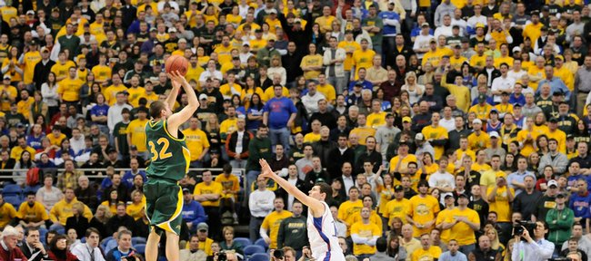 Kansas guard Tyrel Reed tires to disrupt a three-point attempt by North Dakota State guard Josh Vaughan in front of a cheering section dominated by Bison fans during the first half Friday, March 20, 2009 at the Metrodome in Minneapolis.