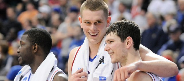 Kansas center Cole Aldrich puts his arm around teammate Tyrel Reed as the seconds waste away in regulation Sunday March 22, 2009 at the Metrodome in Minneapolis. At left is forward Mario Little.