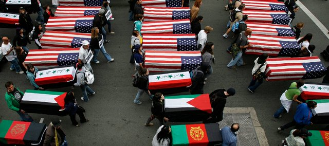 Anti-war activists carry mock coffins draped with American and foreign flags as they march through the Hollywood area of Los Angeles protesting against the wars in Iraq and Afghanistan on Saturday, the sixth anniversary of the start of the war in Iraq.