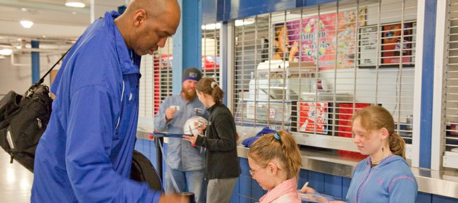 Danny Manning signs autographs for 10 year-old Anastasia Graves and her sister Maria, 12, at Allen Fieldhouse as the KU men's basketball team leaves for Indianapolis.