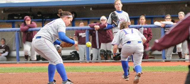 Kansas University pitcher Sarah Blair, left, can't get a handle on a ground ball that gets past third baseman Val Chapple. KU fell to Missouri State, 13-8, on Tuesday at Arrocha Ballpark.