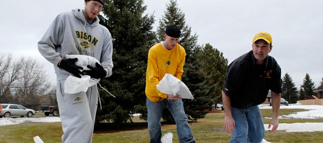 Bison basketball players Sam Sussenguth, left, and Michael Tveidt join Coach Saul Phillips in stacking sandbags in Briarwood, N.D., earlier this week as the Red River and its tributaries continued to rise.