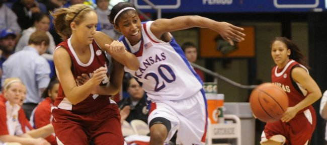KU's Sade Morris knocks the ball away from Arkansas player Julie Inman in the first half of a third-round WNIT game against Arkansas Thursday, March 26, 2009, at Allen Fieldhouse.
