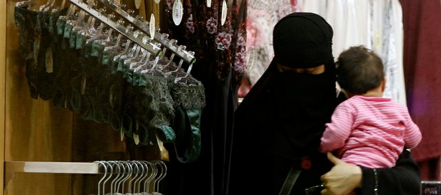 A Saudi woman holding a child checks out lingerie Wednesday at a store in Riyadh, Saudi Arabia. A group of Saudi woman launched a campaign Tuesday aimed at bringing in female sales personnel at lingerie stores. Only men are allowed to sell underwear in almost all stores in this ultraconservative kingdom, making the experience of shopping for intimate apparel embarrassing for most women.