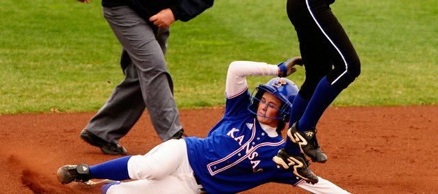 Kansas University's Kolby Fesmire slides into second base safely as Michelle Koch catches the ball on Wednesday at Arrocha Ballpark.