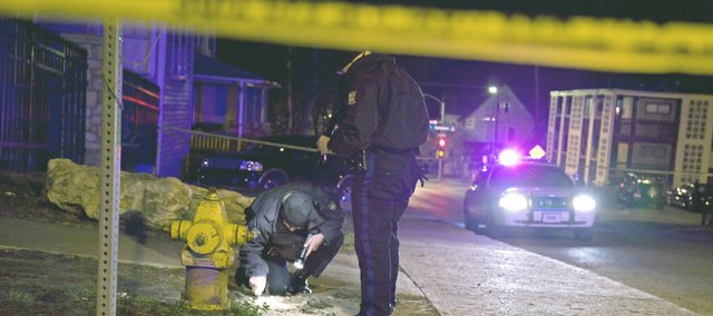 Lawrence police officers gather evidence outside The Hawk, a popular student bar located near the KU campus, after three people were shot, injuring two.