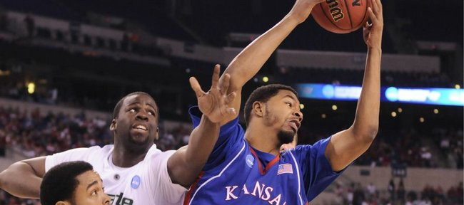 Kansas forward Markieff Morris rips a rebound away from Michigan State defenders Chris Allen, front, and Draymond Green during the first half Friday, March 27, 2009 at Lucas Oil Stadium in Indianapolis.