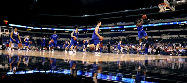 A procession of Jayhawks charge up the court during their first practice Thursday at Lucas Oil Stadium in Indianapolis.