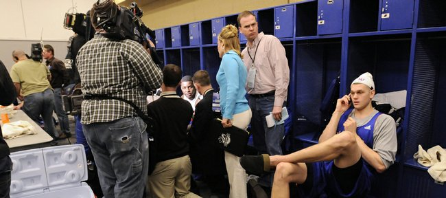 Kansas center Cole Aldrich talks on his cell phone in a pair of house slippers as his teammate Sherron Collins is surrounded by media members in the Jayhawks' locker room Thursday, March 26, 2009 at Lucas Oil Stadium in Indianapolis.