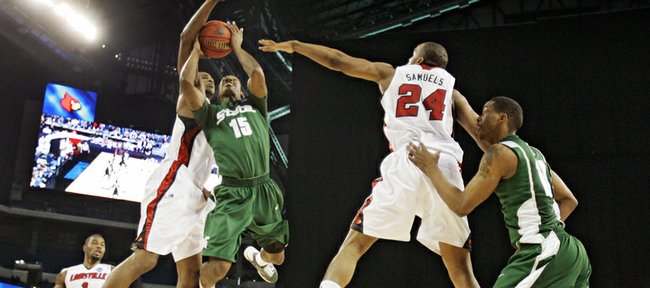 Michigan State's Durrell Summers (15) shoots against Louisville's Samardo Samuels (24) and Andre McGee, second from left,, in the first half of the NCAA Midwest Regional men's college basketball tournament final Sunday, March 29, 2009, in Indianapolis.