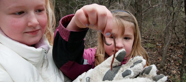 Quail Run School second-graders Ashley Coup, left, and Caitlynn Grammer show off the large worm they found under a log during an outing in the woods Friday with their class. It is the goal of the Nature Education for Kids Task Force to provide children with more opportunities to enjoy and learn from being in natural settings.
