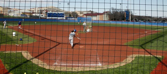 "The Kansas University women's softball team practices at Arrocha Ballpark on Monday while, across campus, university and athletics officials met with the public to discuss a plan to build an ""Olympic Village"" sports complex at KU."