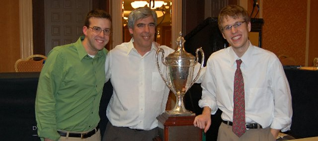 Brett Bricker, from left, KU debate coach Scott Harris, and Nate Johnson surround the national championship trophy that Bricker and Johnson won Tuesday in Texas.
