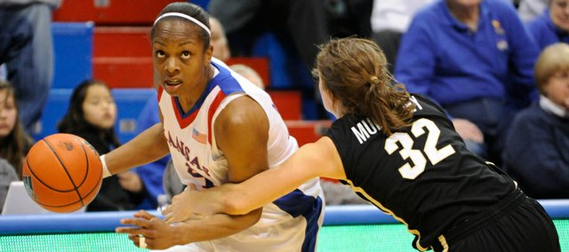 Kansas junior Danielle McCray, left, takes the ball to the basket against Colorado's Kelly Jo Mullaney in this Feb. 4 file photo at Allen Fieldhouse. McCray has led the Jayhawks to three straight WNIT victories.