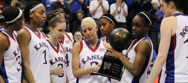 The Kansas women's basketball team holds up the WNIT runner-up trophy. South Florida won the title, 75-71, on Saturday at Allen Fieldhouse.