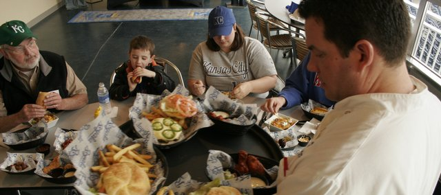 Tom Hilger, his grandson Haris Hilger, 5, and Ronda Davis, all of Lawrence, sample foods from the new culinary venues at Kauffman Stadium. In the foreground is stadium chef Michael Slavin.