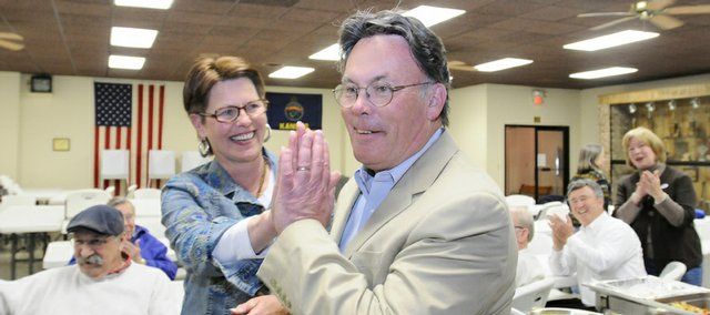 Mike Amyx, who received the most votes in the city commission race, gets a high five from steering committee member and supporter Becky Mondi, Lawrence, as the final numbers are announced during his watch party at the American Legion Tuesday, April 7, 2009.