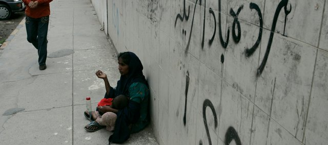 "A Pakistani woman begs Wednesday beneath graffiti reading ""Down with America"" in Lahore, Pakistan. A missile strike Wednesday in Pakistan could strain American-Pakistani ties."