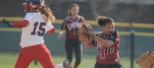 Lawrence High shortstop Jamie Jarrett looks to first base after tagging out Olathe North runner Mo O'Connor on a force out during the second inning. Lawrence High lost the doubleheader, 3-0, 6-2, on Tuesday at Holcom.
