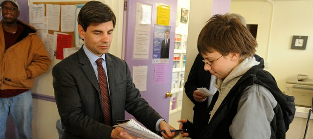 Political commentator George Stephanopoulos, stopped at the Lawrence Community Shelter, 214 W. 10th St., for a walk-through visit during a trip to the city Tuesday, and took a moment to sign an autograph for Aaron Morrison, 12. Stephanopoulos spoke at Kansas University later Tuesday.