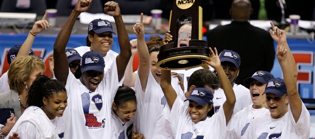 Connecticut players raise the trophy after beating Louisville, 76-54, in the NCAA women's championship game on Tuesday in St. Louis. UConn finished the season 39-0.