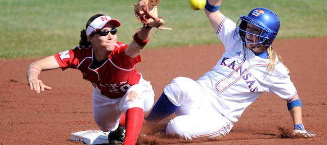 Kansas runner Dougie McCaulley slides into second, beating the throw to Nebraska's Whitney Barrett, left. KU split a doubleheader with the Huskers on Wednesday at Arrocha Ballpark.