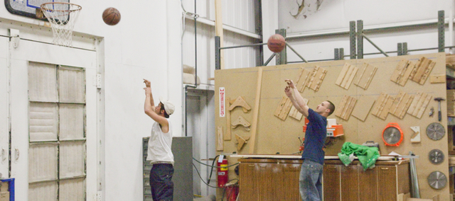 Cabinet makers Leonard Higgins, left, and Cody Robertson pass some down time Friday by shooting hoops on a basketball court they have improvised at Tolar Cabinets. Work orders are down due to the recession.