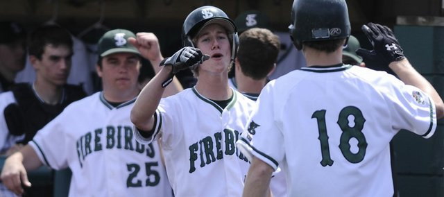 Free State's Connor Stremel, center, celebrates with teammate Ryan Scott after Scott scored a run during the fourth inning Saturday, April 11, 2009.