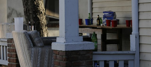 Cups, beer bottles and boxes are strewn about the front porch of a house on the 1300 block of Ohio Street Saturday morning, April 11, 2009.