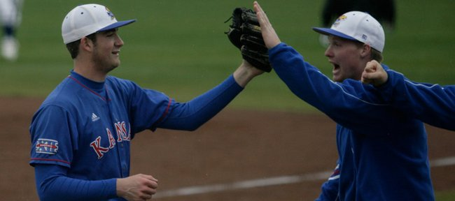Kansas University pitcher Lee Ridenhour, left, leads the Jayhawks off the field after pitching out of a bases-loaded jam against Oklahoma State. The Jayhawks beat the Cowboys, 4-3 in 10 innings, on Sunday at Hoglund Ballpark.