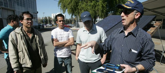 David McFeely talks to students about a sun path analyzer during a recent class on solar panel installation at San Jose City College in San Jose, Calif. Students and colleges are betting that President Barack Obama's campaign to promote alternative energy and combat global warming will create millions of green jobs that pay well, cannot be outsourced and do not require a four-year degree.