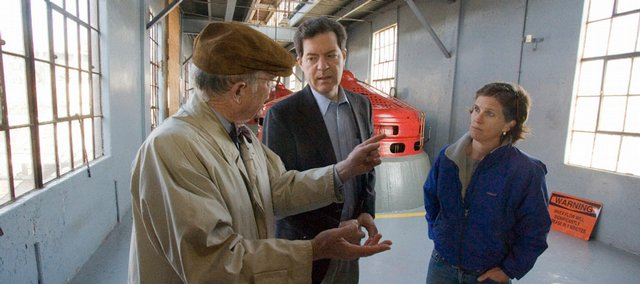 Sen. Sam Brownback, center, gets a guided tour of the Bowersock Mills and Power Co. Brownback touted renewable energy sources like hydroelectricity during a stop in Lawrence on Tuesday. Owner-operators Stephen Hill, left, and Sarah Hill-Nelson answered Brownback's questions.