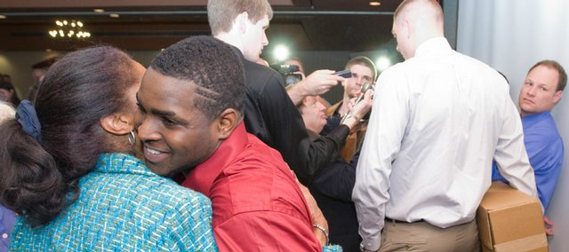 Kansas guard Sherron Collins (in red) gets a hug from Representative Barbara Ballard as center Cole Aldrich (in white) talks with media members after the KU basketball awards banquet. Collins and Aldrich announced at the banquet Monday at the Holidome that they would return to KU next season and not jump to the NBA.